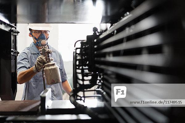 Männlicher Arbeiter lackiert Bauteile schwarz in Spritzkabine einer Kranfabrik  China