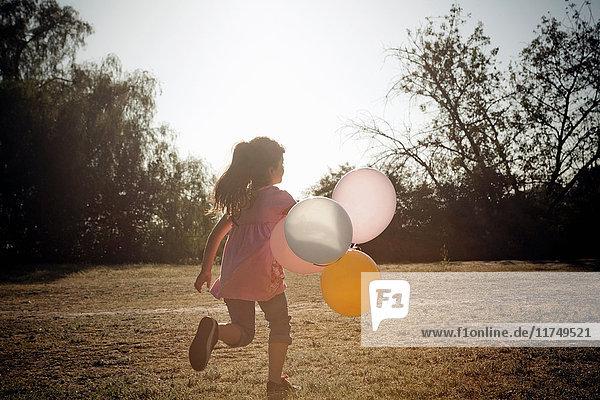 Mädchen läuft mit Luftballons