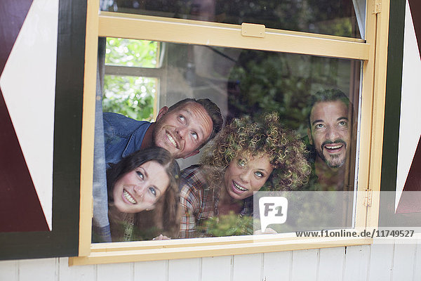 Four adult friends posing whilst looking through cabin window
