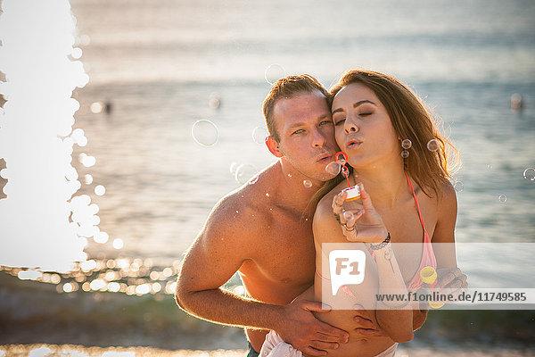 Junges Paar bläst Seifenblasen am Strand  Kastilien  Sardinien  Italien