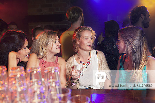 Group of young women chatting in club