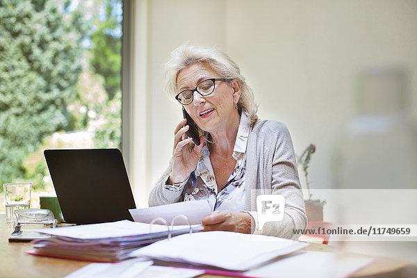 Senior woman sitting at table  looking through paperwork  using smartphone