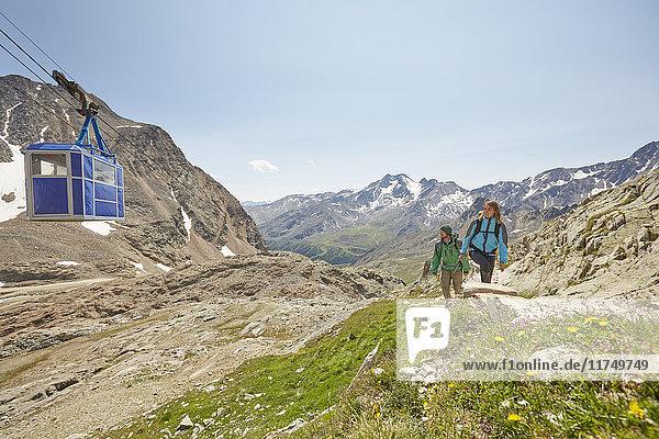 Young hiking couple and cable car at Val Senales Glacier  Val Senales  South Tyrol  Italy