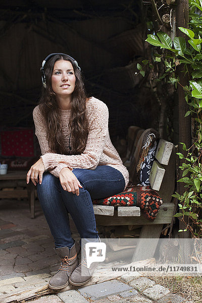 Young woman sitting in garden porch listening to headphone music