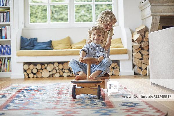 Zwei junge Brüder spielen mit einem Holzspielzeugauto