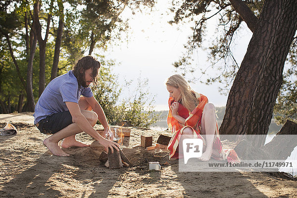 Young couple making campfire by lake