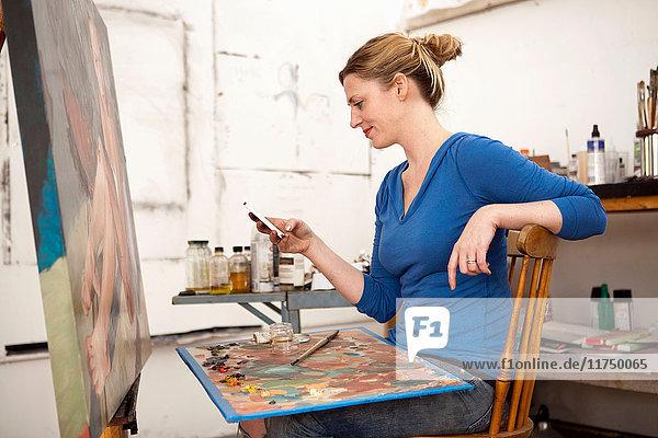 Mittlere erwachsene Frau benutzt Mobiltelefon im Künstleratelier