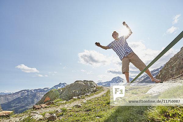 Young man balancing on slackline at Val Senales Glacier  Val Senales  South Tyrol  Italy