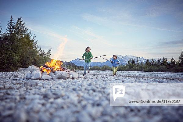 Frontansicht von Jungen  die mit Stöcken zum Lagerfeuer rennen  Wallgau  Bayern  Deutschland