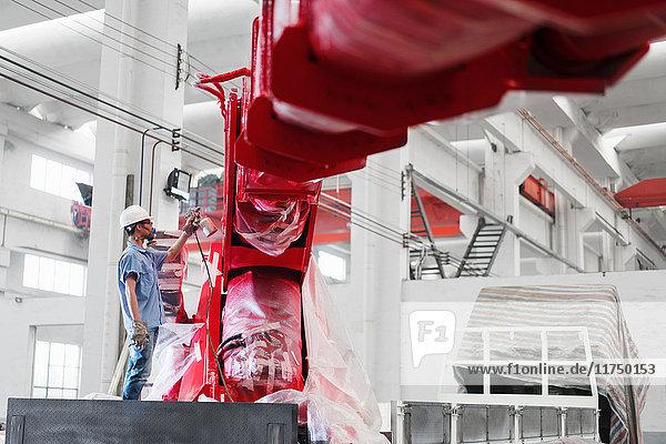 Männlicher Fabrikarbeiter besprüht einen Kranarm in einer Fabrikhalle rot  China