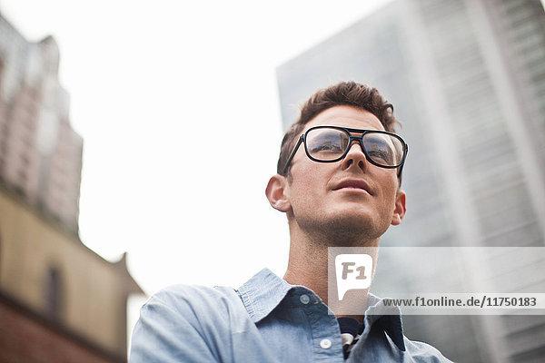 Junger Mann mit Brille schaut weg  niedriger Blickwinkel