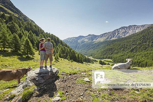 Rückansicht eines jungen Paares  das auf einem Felsblock steht und auf die Berge blickt  Schnalstal  Südtirol  Italien