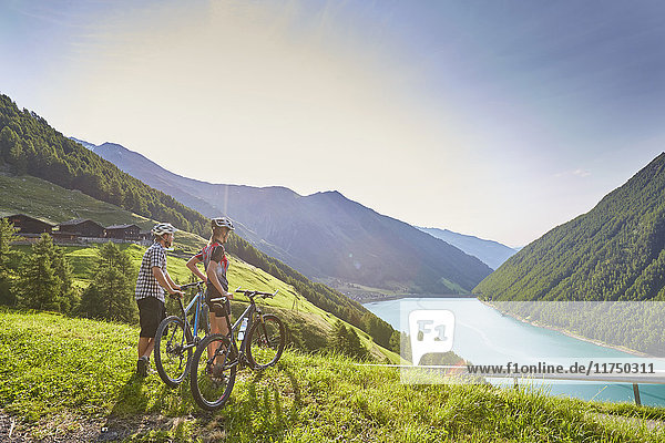 Young mountain biking couple looking out over Vernagt reservoir and Finailhof farmhouse  Val Senales  South Tyrol  Italy