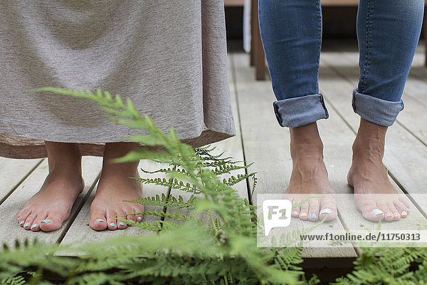 Painted toenails of couple standing on cabin porch