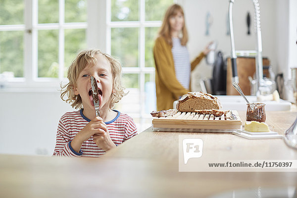 Mother and son in kitchen  son licking knife with chocolate on it
