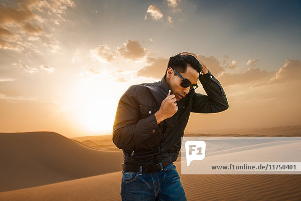 Man with hand in hair  Glamis sand dunes  California  USA