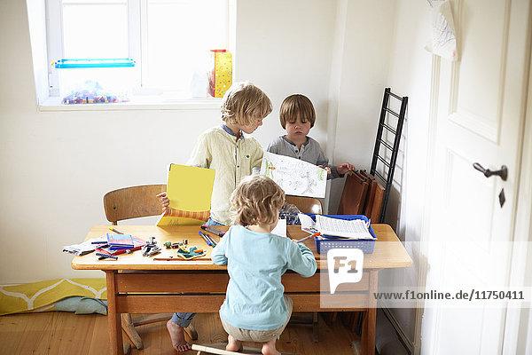 Drei Jungen sitzen am Tisch und zeichnen Bilder