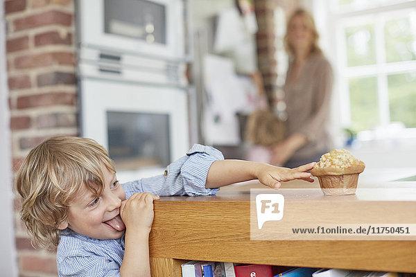 Junge versucht  Muffin auf dem Küchentisch zu erreichen