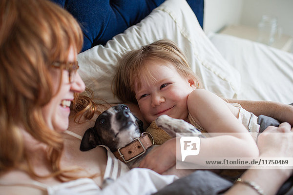 Mother  daughter and dog lying in bed