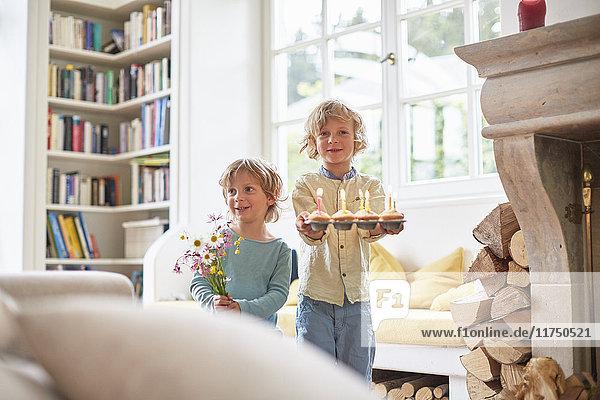 Zwei Jungen halten Blumen und Törtchen mit brennenden Kerzen