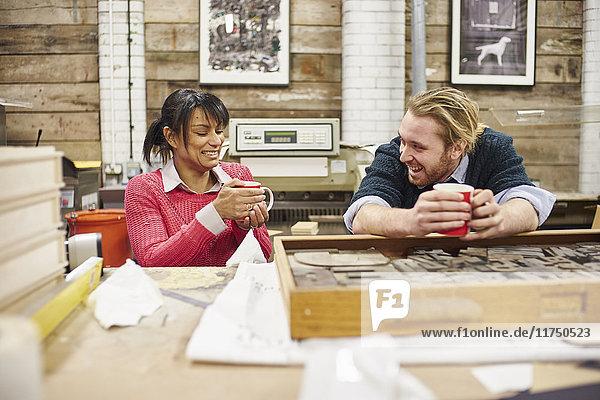 Drucker und Druckerinnen plaudern und trinken Kaffee in traditioneller Druckwerkstatt