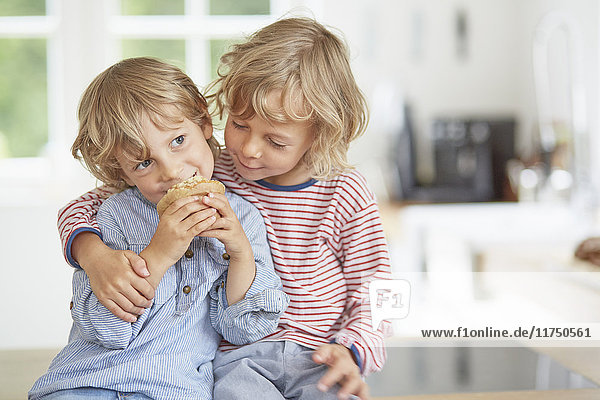 Young boy eating muffin while his brother looks on