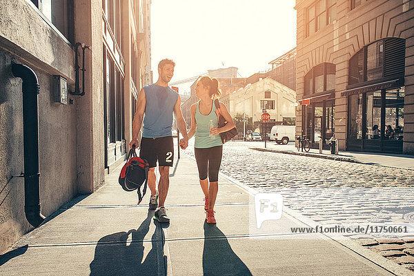Junges Paar  das nach der Ausbildung auf der Straße Händchen hält