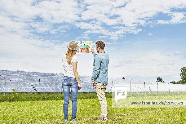 Junges Paar steht auf einem Feld und betrachtet die Zeichnung eines Kindes von einem Haus neben einem Solarpark