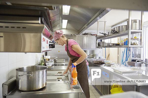 Reife Frau mit Schürze und Kopftuch reinigt Küchenherd