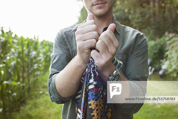 Cropped shot of mid adult man folding blanket in field