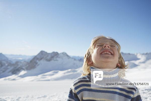 Porträt eines Jungen in verschneiter Landschaft  der aufschaut und lächelt
