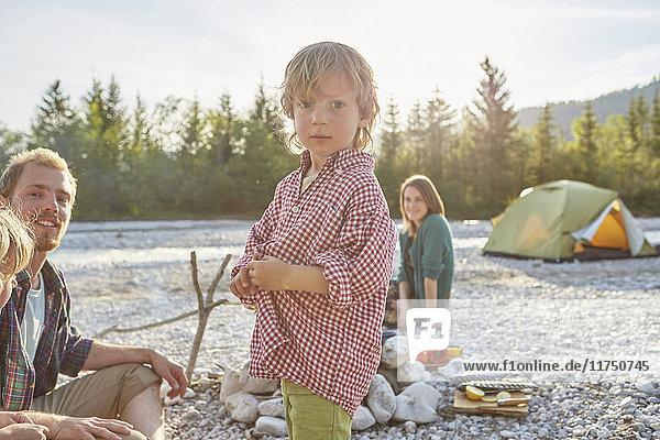 Porträt eines Jungen mit Eltern auf Campingreise  der in die Kamera schaut
