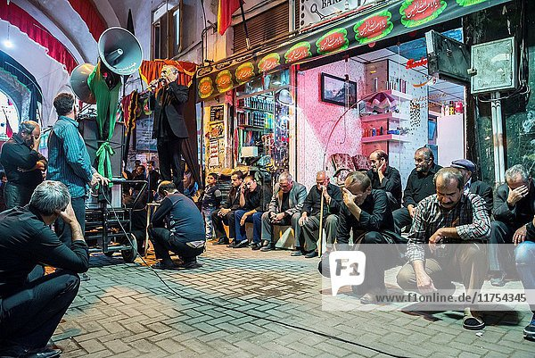 Man praying and singing to honour Husayn ibn Ali during Muharram month on the old Bazaar of Kashan city  capital of Kashan County in Iran.