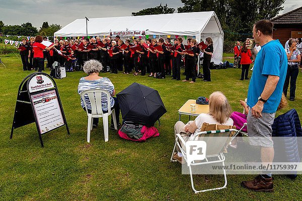 Local People Watch A Community Choir Singing In The Rain At The Maresfield Fete  Maresfield  East Sussex  UK.