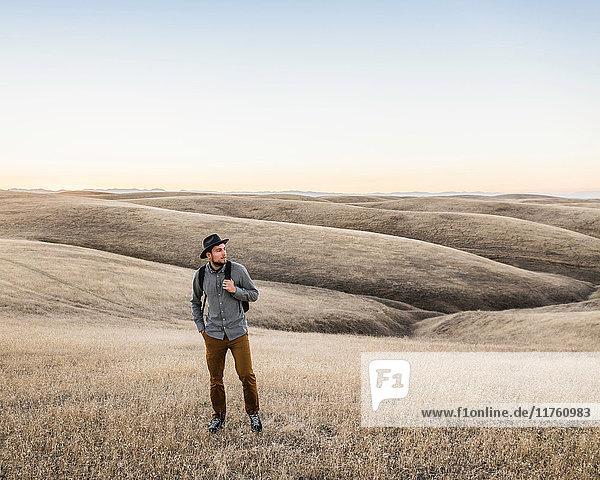Mann schaut auf sanfte Präriehügel  Bakersfield  Kalifornien  USA