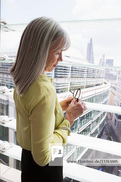 Geschäftsfrau  die am Fenster im Büro steht  London  UK Geschäftsfrau, die am Fenster im Büro steht, London, UK