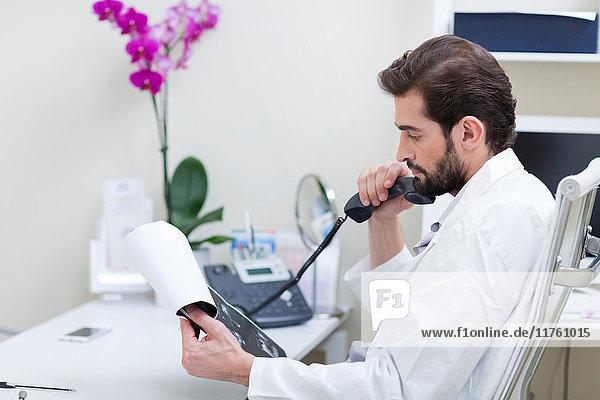 Arzt am Schreibtisch beim Telefonieren