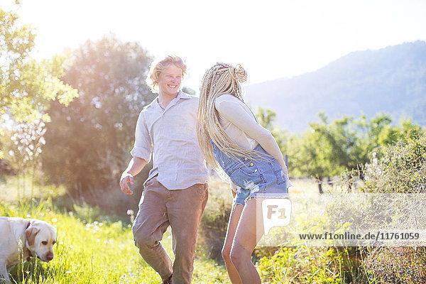 Junges Paar lacht beim Hundespaziergang auf dem Land  Mallorca  Spanien