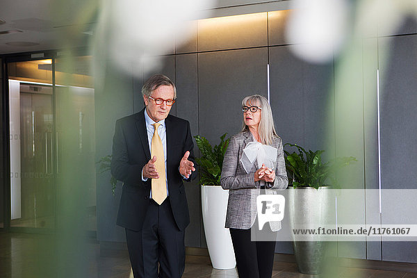 Businessman and businesswoman having discussion while walking