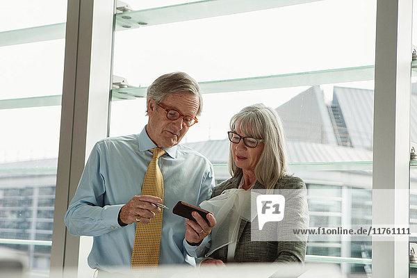Geschäftsmann und Geschäftsfrau lesen Nachricht auf Mobiltelefon Geschäftsmann und Geschäftsfrau lesen Nachricht auf Mobiltelefon