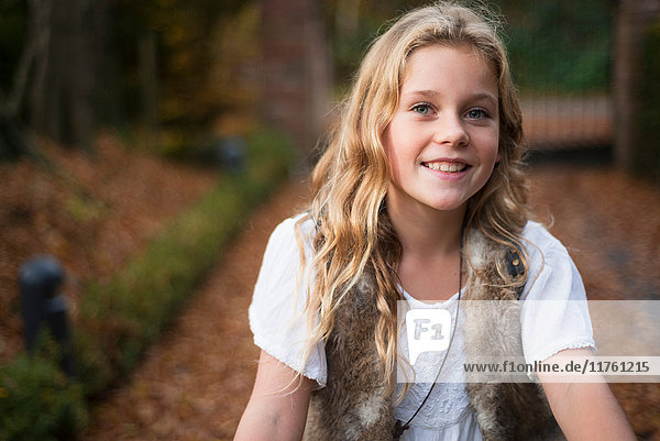 Portrait of blond haired girl in autumn park