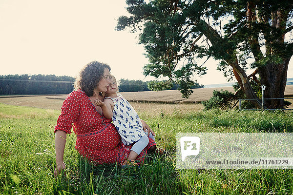 Pregnant woman sitting in field with toddler daughter on lap