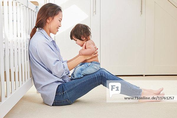 Frau sitzt auf dem Boden und spielt mit ihrer kleinen Tochter auf dem Schoss