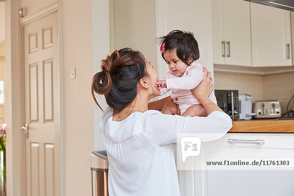 Woman holding baby daughter on kitchen counter