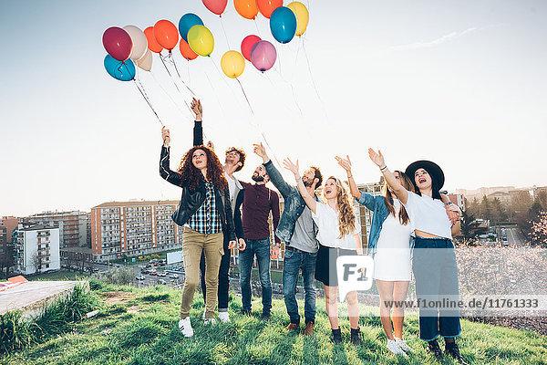 Porträt einer Gruppe von Freunden  die auf dem Dach stehen und Heliumballons halten