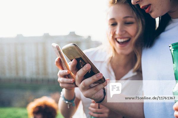 Zwei junge Frauen im Freien  die sich Smartphones anschauen