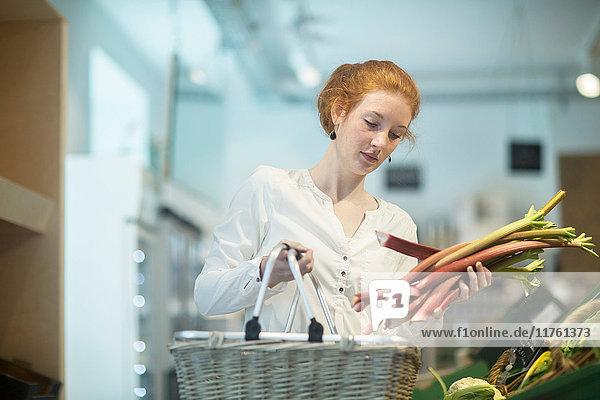 Frau im Geschäft mit Einkaufskorb und Rhabarber