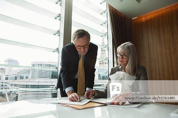 Geschäftsmann und Geschäftsfrau lesen und analysieren Bericht  London  UK Geschäftsmann und Geschäftsfrau lesen und analysieren Bericht, London, UK
