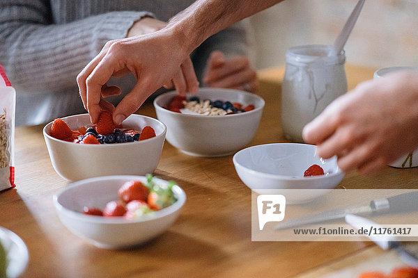Hände eines jungen Paares bei der Zubereitung eines Obstfrühstücks an der Küchentheke