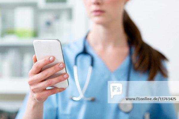 Arzt im Krankenhaus schaut auf Handy